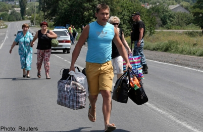 Local residents carry their belongings as they flee from what they say was shelling by Ukrainian forces, in the town on the suburbs of Shakhtarsk, Donetsk region, July 28, 2014. - Reuters